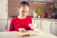 Libro de lectura del adolescente con una taza de té Foto de archivo libre de regalías