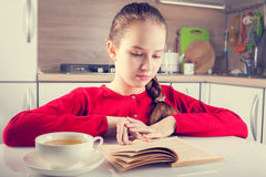 Libro de lectura del adolescente con una taza de té Fotografía de archivo