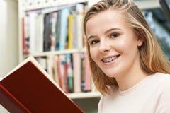 Libro de lectura del adolescente en casa Fotografía de archivo