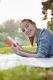 Libro de lectura del adolescente en el parque Imagen de archivo