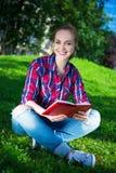 Libro de lectura del adolescente en parque Fotos de archivo
