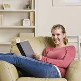 Libro de lectura del adolescente en silla Imagen de archivo