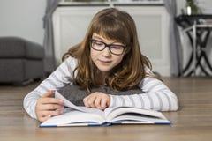 Libro de lectura del adolescente mientras que miente en piso en casa Fotografía de archivo
