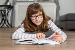 Libro de lectura del adolescente mientras que miente en piso en casa Imagen de archivo