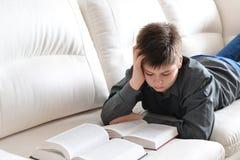 Libro de lectura del adolescente que miente en el sofá en sitio Imagenes de archivo