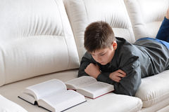 Libro de lectura del adolescente que miente en el sofá en sitio Imagen de archivo