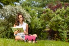 Libro de lectura del adolescente que se sienta en parque Imágenes de archivo libres de regalías