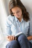 Libro de lectura del adolescente que se sienta por la ventana Fotografía de archivo libre de regalías