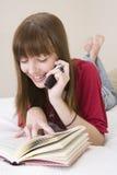 Libro de lectura del adolescente y el hablar en un teléfono Imágenes de archivo libres de regalías