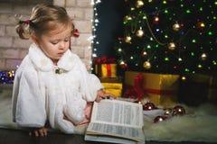 Libro de lectura del bebé con cuento de hadas en la Navidad foto de archivo