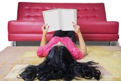 Libro de lectura del estudiante de la High School secundaria en la alfombra Imagen de archivo