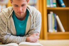 Libro de lectura del estudiante masculino en el piso de la biblioteca de universidad Fotografía de archivo libre de regalías