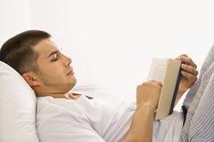 Libro de lectura del hombre en cama. Imagen de archivo libre de regalías