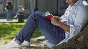 Libro de lectura del hombre joven atento empathizing y que se preocupa con los caracteres principales almacen de video