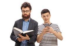 Libro de lectura del hombre joven con el adolescente que mira el teléfono Imagen de archivo