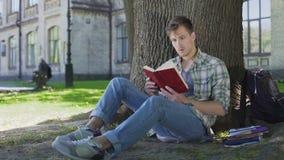 Libro de lectura del hombre joven con el argumento fascinador, empathizing con los caracteres almacen de metraje de vídeo