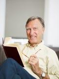 Libro de lectura del hombre mayor fotografía de archivo