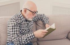 Libro de lectura del hombre mayor en casa, espacio de la copia Imagenes de archivo