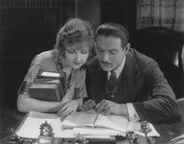 Libro de lectura del hombre y de la mujer en el escritorio fotografía de archivo