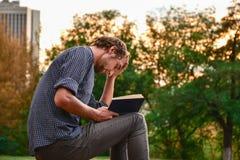 Libro de lectura del individuo en parque Fotografía de archivo libre de regalías
