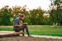 Libro de lectura del individuo en parque Foto de archivo