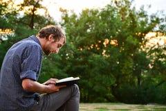 Libro de lectura del individuo en parque Imagen de archivo