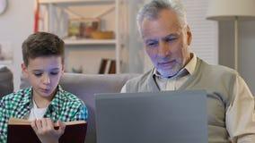 Libro de lectura del muchacho, abuelo que usa el ordenador portátil en casa, educación en diversa edad metrajes