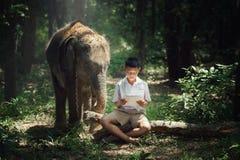 Libro de lectura del muchacho con el amigo del elefante Foto de archivo libre de regalías