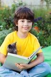 Libro de lectura del muchacho con el gatito en la yarda, niño con la lectura del animal doméstico Imagen de archivo libre de regalías