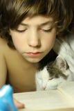 Libro de lectura del muchacho del adolescente con el gato en cama Fotos de archivo libres de regalías
