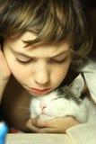 Libro de lectura del muchacho del adolescente con el gato en cama Foto de archivo libre de regalías