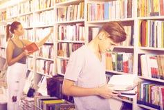 Libro de lectura del muchacho del adolescente en tienda Imágenes de archivo libres de regalías