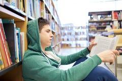Libro de lectura del muchacho del estudiante o del hombre joven en biblioteca Fotografía de archivo