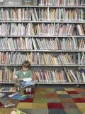 Libro de lectura del muchacho en biblioteca Imágenes de archivo libres de regalías