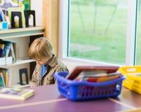 Libro de lectura del muchacho en biblioteca Imagen de archivo