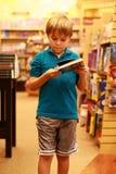 Libro de lectura del muchacho en la biblioteca o el almacén de libro Fotos de archivo libres de regalías