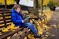 Libro de lectura del muchacho que se sienta en parque del otoño Foto de archivo libre de regalías