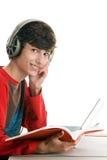 Libro de lectura del muchacho y el escuchar la música Imágenes de archivo libres de regalías