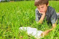 Libro de lectura del niño al aire libre Imágenes de archivo libres de regalías