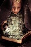 Libro de lectura del niño bajo cubiertas con la linterna Imagenes de archivo