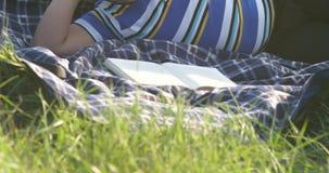 Libro de lectura del niño pequeño él es mentiras en la alfombra en el movimiento liso de la cámara de la hierba metrajes