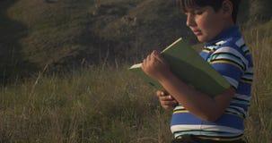 Libro de lectura del niño pequeño él es se sienta en piedra almacen de video