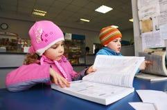 Libro de lectura del niño pequeño y de la muchacha Imagen de archivo