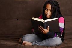Libro de lectura del niño que se sienta en el sofá Fotos de archivo libres de regalías