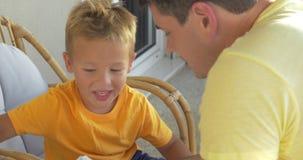 Libro de lectura del niño y del padre en el balcón almacen de video