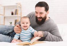 Libro de lectura del padre a poco hijo del bebé fotos de archivo