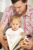 Libro de lectura del padre y del bebé Fotografía de archivo libre de regalías