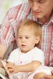 Libro de lectura del padre y del bebé Fotografía de archivo