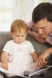 Libro de lectura del padre y del bebé en el sofá Fotografía de archivo