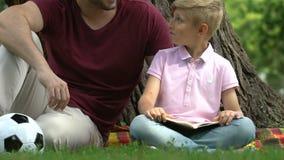 Libro de lectura del papá y del niño, padre que explica los artículos difíciles al hijo, educación almacen de metraje de vídeo